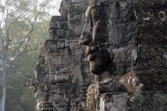 De antropomorfe gezichten sneden in steen in Bayon Wat, een de 12de eeuwtempel binnen Angkor Thom comp stock afbeelding