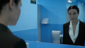 De apathie, gefrustreerde jonge vrouw in openbaar toilet gaat haar oogglazen van start en bekijkt zich in spiegel