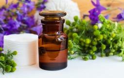 De apotheekfles met kosmetische/reinigende/helende kruiden van het van de olietint, infusie, uittreksel en katoenen stootkussens  royalty-vrije stock foto's
