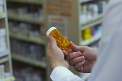 De apotheker onderzoekt een fles van vitaminen Stock Foto