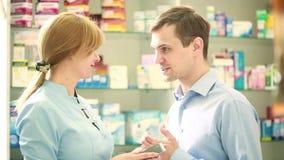 De apothekervrouw biedt de bezoeker een behandeling bij de apotheek aan stock footage