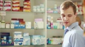 De apothekervrouw biedt de bezoeker een behandeling bij de apotheek aan stock videobeelden