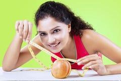 De appel van vrouwenmaatregelen met een maatregelenband royalty-vrije stock afbeelding