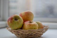 De appelen liggen in een rieten mandclose-up royalty-vrije stock afbeeldingen