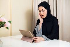 De Arabische dame met hijab schokte terwijl het gebruiken van een tabletcomputer stock afbeelding