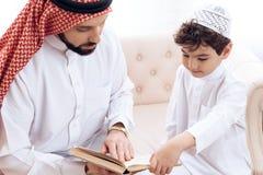 De Arabische gebaarde mens leest boek met kleine zoon royalty-vrije stock afbeeldingen