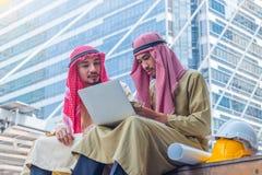 De Arabische ingenieur die over bouwbaan spreken met laptop op achtergrond van de binnenstad en de de bouw stock afbeelding