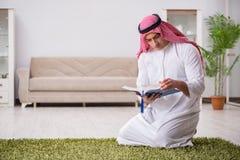 De Arabische man die thuis bidden Stock Afbeelding