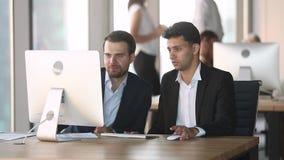 De Arabische manager instrueert Kaukasische nieuwe arbeiderscollega met computer stock footage