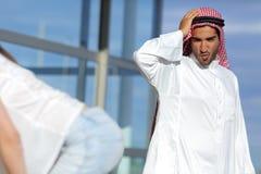 De Arabische mens die verbaasde een sexy meisjesuiteinde in de straat kijken Stock Foto
