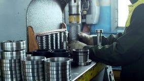 De arbeider assembleert het drukken van het lager in een metaalklem op de machine, assembleert de gebeëindigde eenheid, close-up stock videobeelden