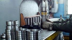 De arbeider assembleert het drukken van het lager in een metaalklem op de machine, assembleert de gebeëindigde eenheid, close-up stock video