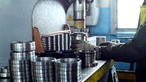De arbeider assembleert het drukken van het lager in een metaalklem op de machine, assembleert de gebeëindigde eenheid, close-up stock footage