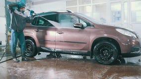 De arbeider in de autodienst wast een auto in het zeepsop door waterslangen