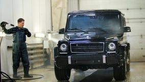 De arbeider in de autodienst wast een luxeauto door waterslangen, backlight