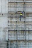 De arbeider beklimt bij de bouw in bouwterrein Royalty-vrije Stock Afbeeldingen