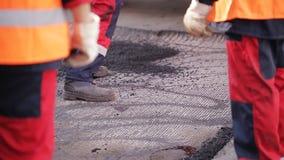 De arbeider bereidt het beschadigde wegsgedeelte voor het asfalteren voor stock footage