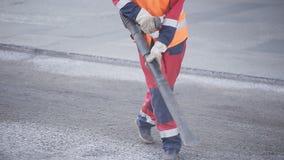 De arbeider bereidt het beschadigde wegsgedeelte voor het asfalteren voor De werkende luchtstraal blaast puin en kleine kiezelste stock footage