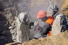 De arbeider bij de bouwwerf snijdt beton stock afbeelding