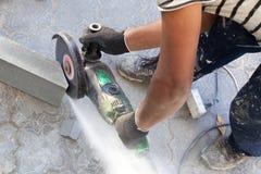 De arbeider bij de bouwwerf zaagt een stuk van concrete rand met hoekmolen, cirkel elektrische zaag, hulpmiddel in de handen van  royalty-vrije stock afbeelding