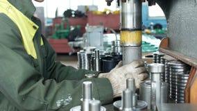 De arbeider bij de installatie drukt het lager in de hub gebruikend een persmachine, assemblerend de hub, assemblerend de eenheid stock footage
