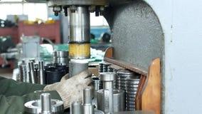 De arbeider bij de installatie drukt het lager in de hub gebruikend een persmachine, assemblerend de hub, assemblerend de eenheid stock videobeelden