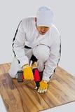 De arbeider boorde houten vloerbarsten Stock Afbeelding