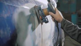 De arbeider borstelt van oude blauwe kleurstof van automobiel lichaam gebruikend handmolen, die voor het schilderen in een autowo stock footage