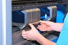 De arbeider buigt een metaalplaat op de machine Stock Fotografie