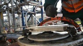 De arbeider controleert en verzegelt Olietank GLB bij Fabriek stock footage