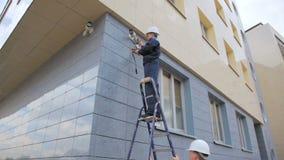 De arbeider controleert kabeltelevisie-de de cameraverrichting en collega ladder houden stock videobeelden