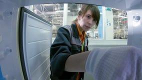 De arbeider controleert koelkast met digitale meter van binnenuit mening stock footage