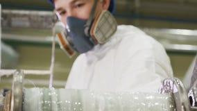 De arbeider controleert machine roterend broodje met plastic stroken stock footage