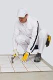 De arbeider controleert oude tegelsbasis met hamer Royalty-vrije Stock Afbeelding