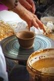 De arbeider creeert kleivoorwerpen op een aardewerkwiel stock fotografie