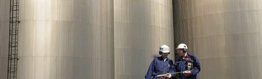 De arbeider, de olie en de brandstof van de industrie stock afbeelding