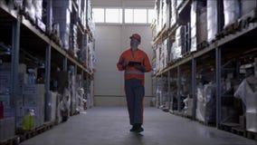 De arbeider die bouwvakker met tabletcomputer dragen in pakhuis loopt door rijen van opslagrekken met koopwaar stock videobeelden