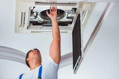 De arbeider die de eenheid van de plafondairconditioning herstellen royalty-vrije stock afbeeldingen
