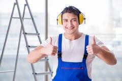 De arbeider die met lawaai hoofdtelefoons annuleren stock afbeelding