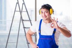 De arbeider die met lawaai hoofdtelefoons annuleren stock fotografie