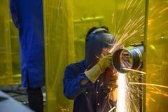 De arbeider die de staalpijp na lassen malen Stock Foto