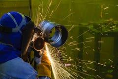 De arbeider die de staalpijp na lassen malen Royalty-vrije Stock Foto
