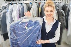 De arbeider die van de meisjeswasserij een hanger houden die met schone kleren wordt ingepakt stock foto's