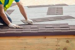 De arbeider die van de Rooferbouwer de Tegels van Asphalt Shingles of van het Bitumen in aanbouw installeren op een nieuw huis royalty-vrije stock afbeeldingen