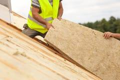 De arbeider die van de Rooferbouwer het materiaal van de dakisolatie in aanbouw installeren op nieuw huis stock afbeelding
