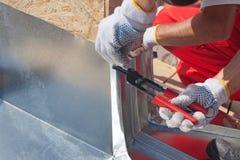De arbeider die van de Rooferbouwer vouwend een metaalblad die speciale buigtang met een grote vlakke greep met behulp van eindig stock foto