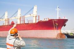 De arbeider die van het havendok op radio spreken Stock Afbeeldingen
