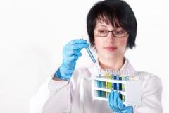 De arbeider die van het laboratorium reageerbuis steunt stock afbeelding