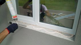 De arbeider dient beschermende handschoenen in toepassend het schuim van de polyurethaanbouw op de close-up van de venstervenster stock videobeelden