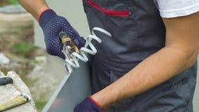 De arbeider dient beschermende handschoenen in voorbereidend pvc-het scherpe metaal van de venstervensterbank met schaarclose-up stock videobeelden